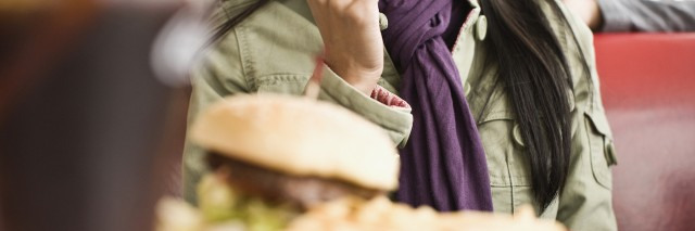 Woman sitting at diner counter, talking and eating
