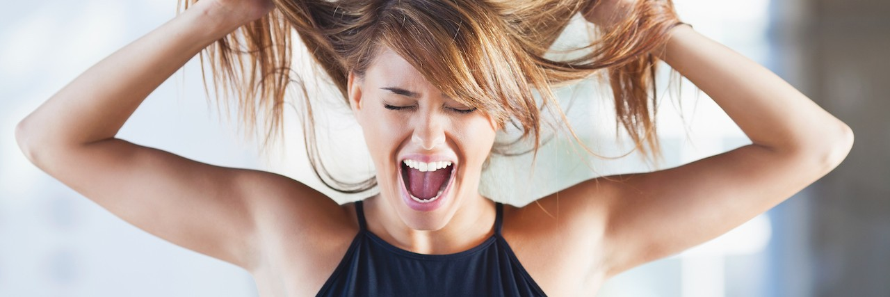 Woman pulling on her hair and screaming