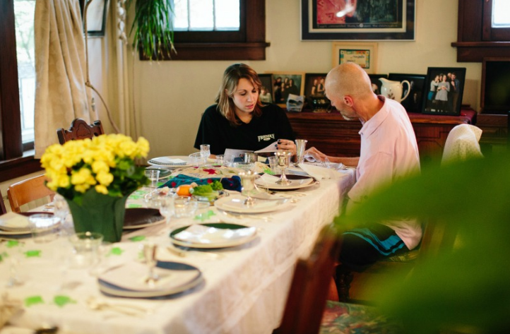 Ray teaches daughter Lisa the Haggadah so she can lead the Seder.