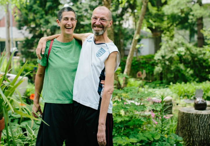 "Ray and Rae stand in the garden outside their home. ""Early on, we promised to laugh every day,"" says Rae. Ray says he's ""smiling every day. Crookedly but smiling, nonetheless."""