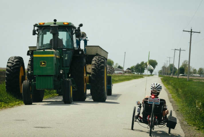 "Ray pedals his trike next to a giant tractor. Ray says, ""[I rode] 31 miles last Tuesday. Not my usual 100, but ALS has given me the time to absorb my surroundings."""