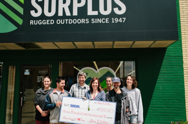 "The Spooners pose in front of Champaign Surplus with a check for MDA. ""When Rae and I sat down to discuss a goal for our MDA fund raiser, we thought $10,000 sounded an attainable amount. Last week we achieved more than we ever thought imaginable, $80,000."""