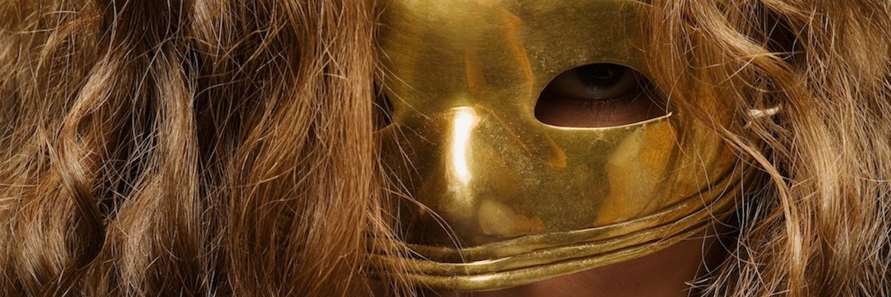 Girl wearing a gold mask.