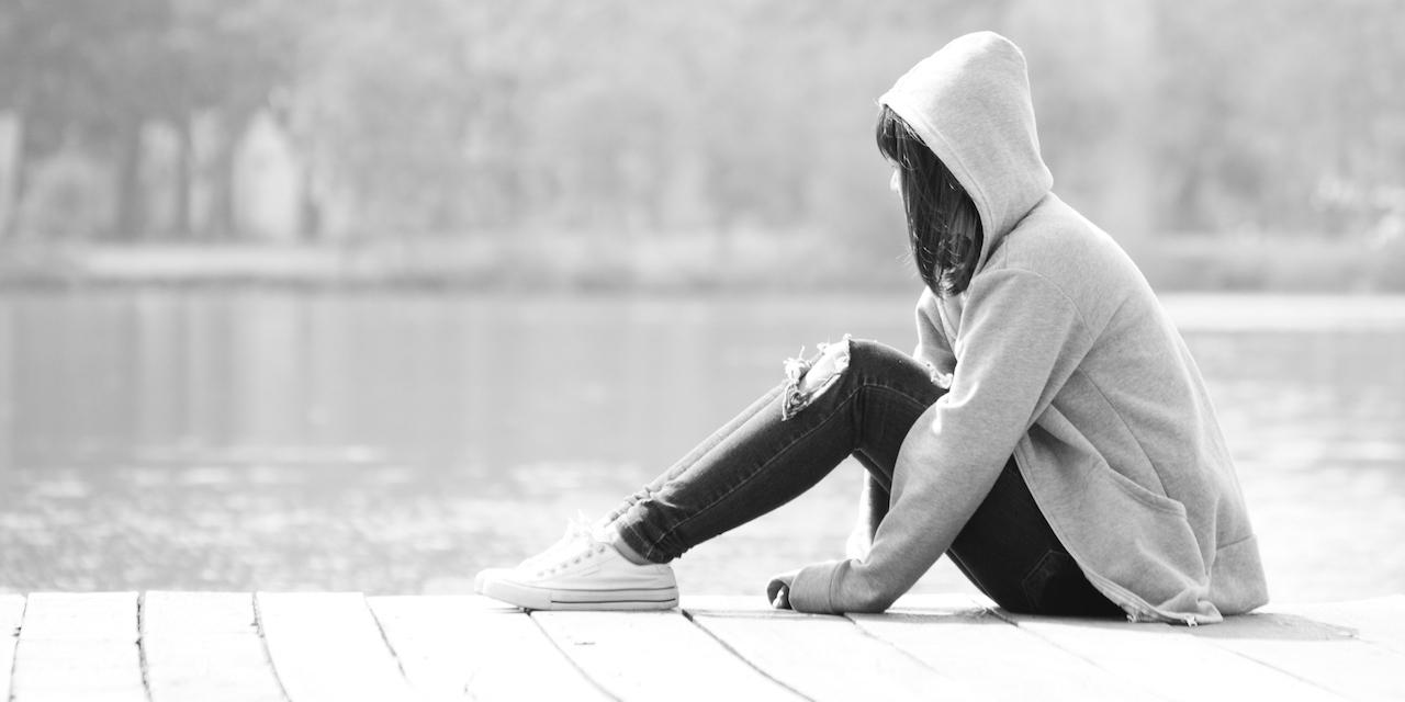 Sad teenage girl sitting alone near river.