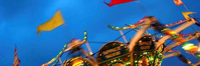 Carnival ride spinning, blurring lights and flags in the night.