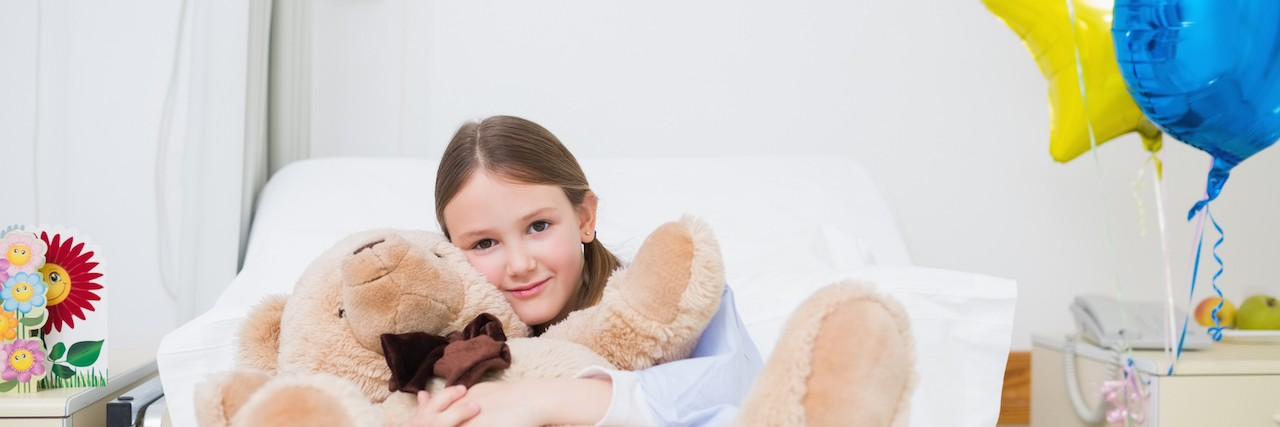 Child hugging a teddy bear in Hospital