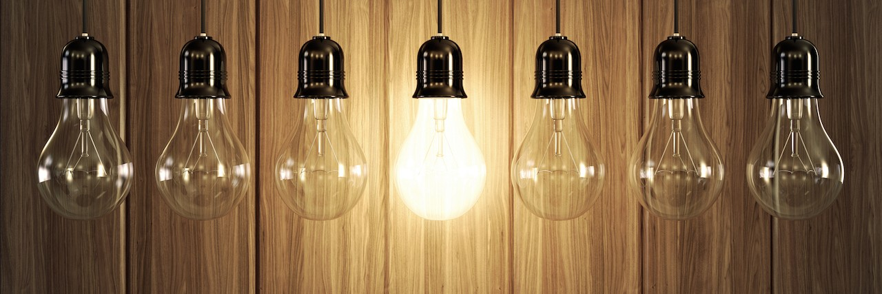 Seven light bulbs with glowing one on wooden background.