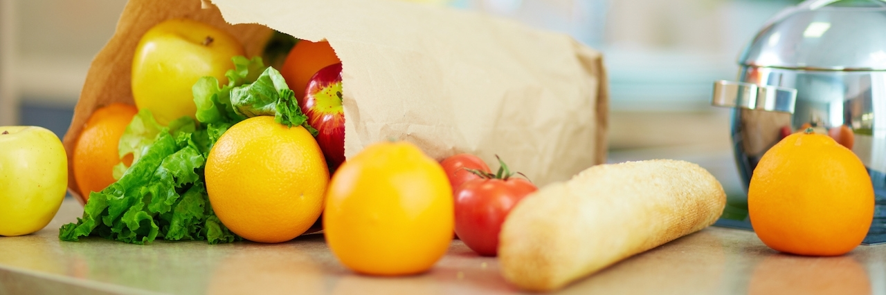 Close-up of paperbag full of fruits and vegs with female on background