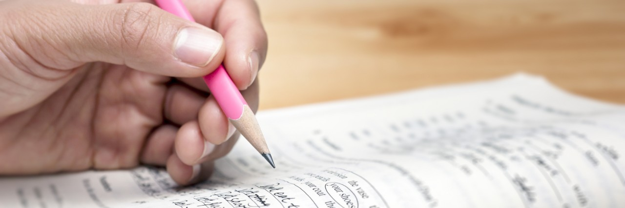 A closeup of a teenager holding a pencil while doing homework.