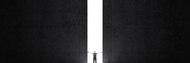 Dark abstract concrete interior. Man stands in the light of opening.