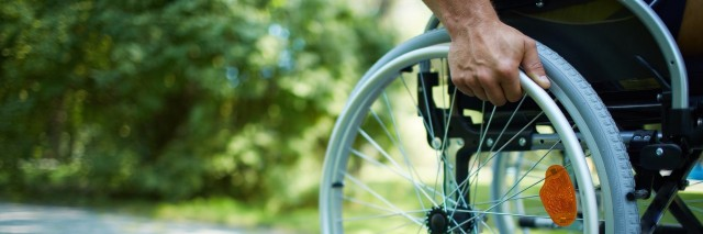 A close-up of a hand pushing a wheelchair.