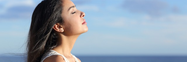 Profile of a beautiful arab woman breathing fresh air in the beach with a cloudy blue sky in the background