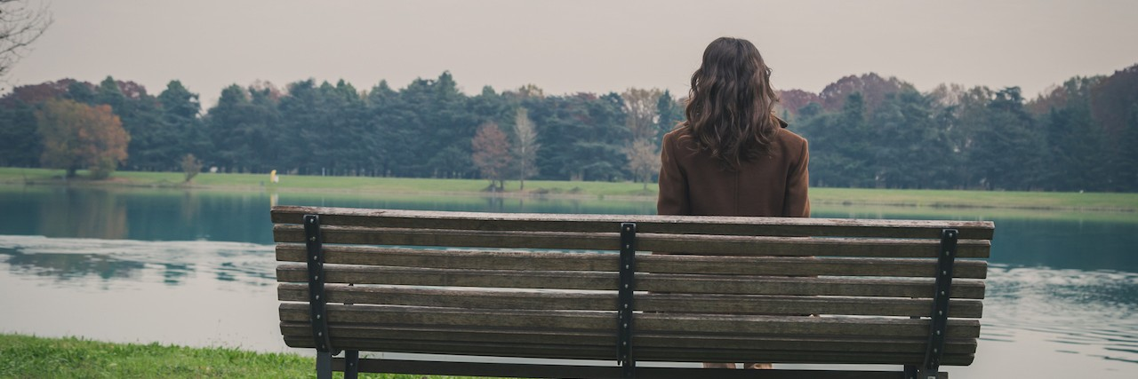 Young woman sitting on a bench in a city park