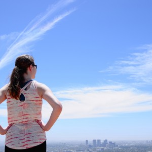Half length portrait of young woman from behind. Woman is wearing sunglasses and a sleeveless shirt. Subject has her hands on her hips and is looking at a city skyline. Image is landscape orientation.