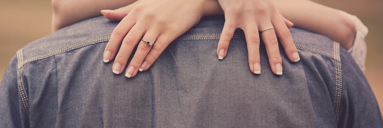 A woman embracing her man with engagement ring on hand.