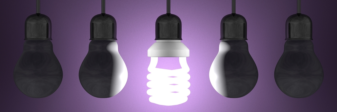 Glowing spiral light bulb among tungsten ones in lamp sockets hanging on dark violet textured background
