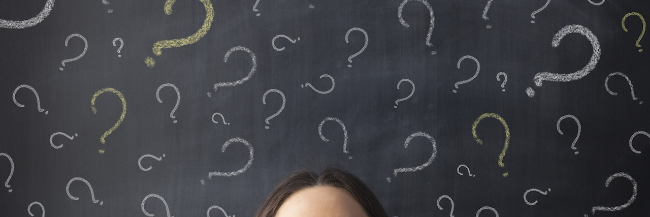 Chalk question marks above businesswoman at blackboard