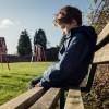 Upset child sitting on play park playground bench