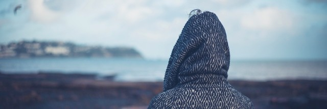 a woman wearing a hoodie looking at water