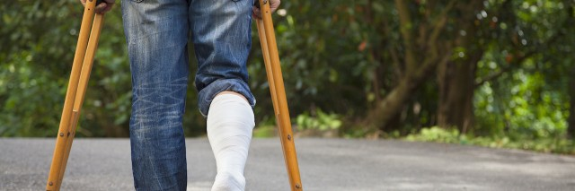 Young man on crutches with tree background on a road