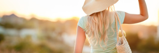 A slender woman,with long blonde hair in a straw hat with large brim,blue shorts and blue t-shirt,on the shoulder woven straw bag,admiring the sunset while standing on the beach near the sea