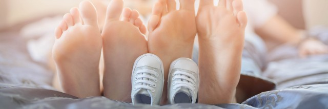 Pregnant mother and future dad feet on bed and little unborn baby shoes