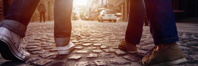 Two People Walking on Cobblestone Street