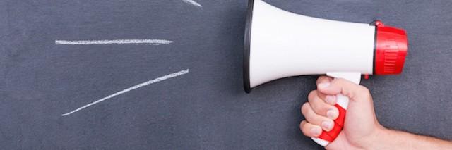 Close-up of human hand holding megaphone against blackboard