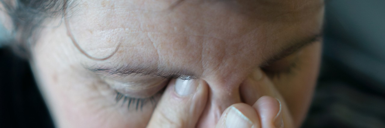 A dark image and close up of a middle aged woman rubbing her eyes and holding her head, as if in anguish, or with a bad headache.