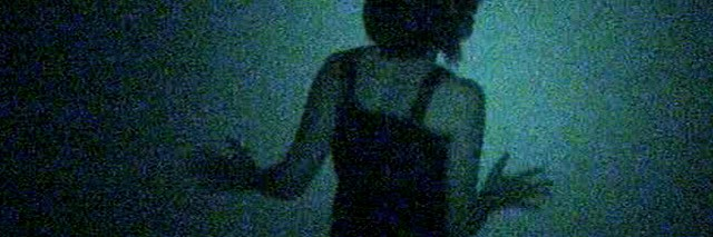 Woman from behind which looks lost in the darkness blue.