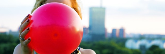 girl holding a red balloon in front of her face
