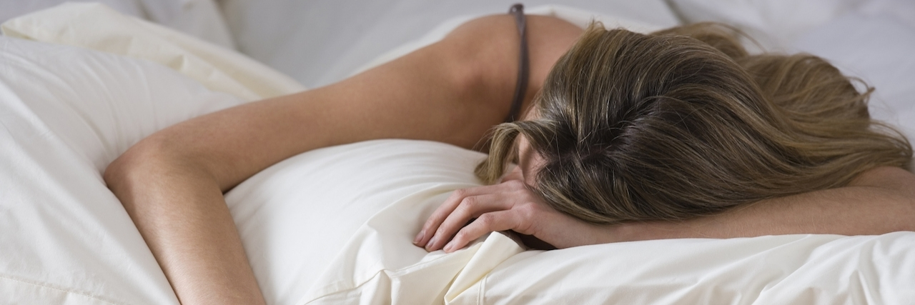 Woman lying in bed with face buried in pillow