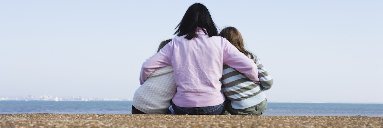 Mother and daughters sitting on a beach