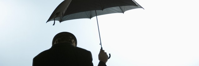 Person with head down holding umbrella