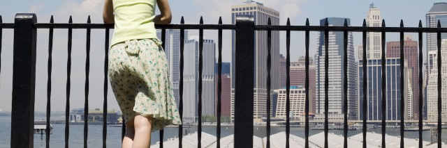 Woman leaning on railing in New York City looking at the skyline