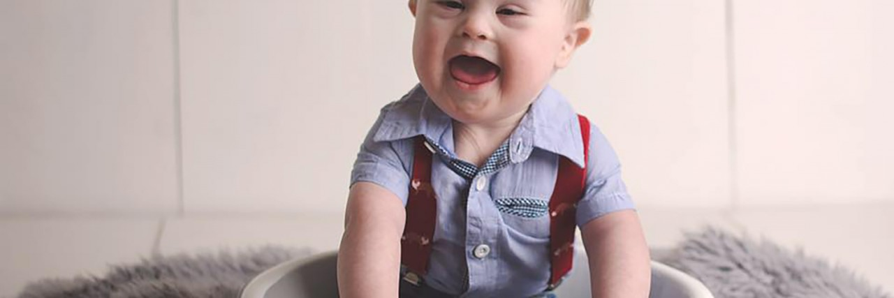 Meagan's son. Toddler with Down syndrome sitting in a bowl and laughing.