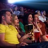 Audience sitting in multiplex movie theater, watching movie.