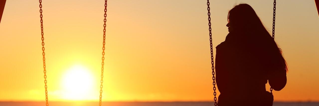 single woman swings alone next to an empty swing