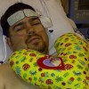 man lying on hospital bed with yellow heart pillow on him