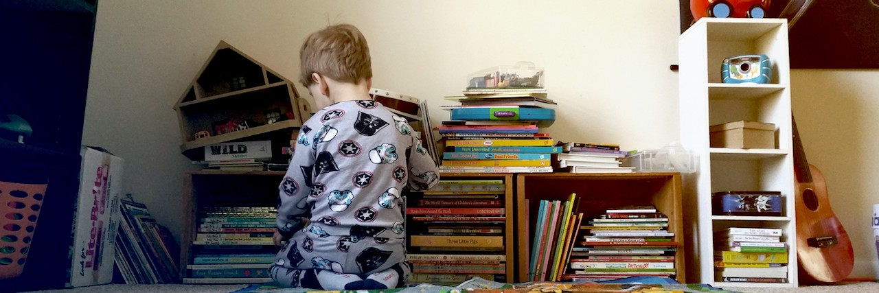 Toddler boy playing in front of books and toys
