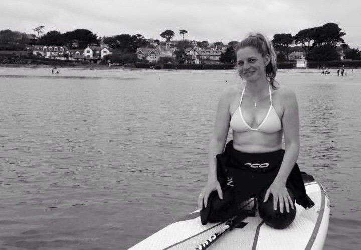 woman sitting on kayak on lake