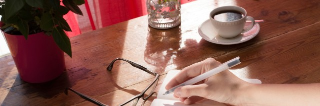 female writing a note in a vintage notebook next to red flowers
