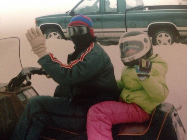 madelyn as a teenager riding a snowmobile with her father