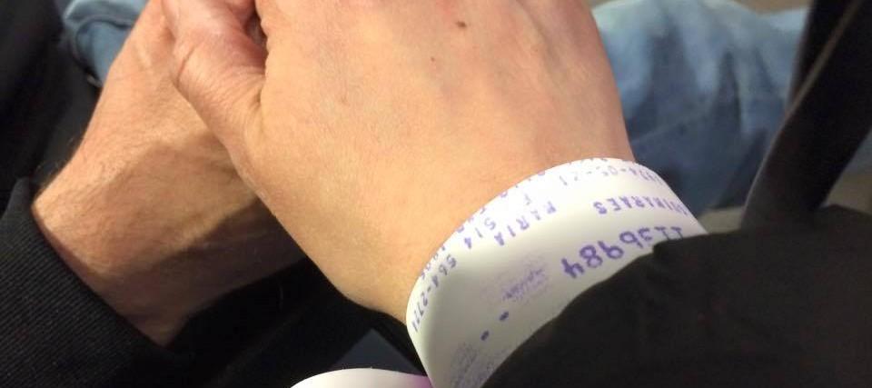 hand wearing hospital bracelet holding hand