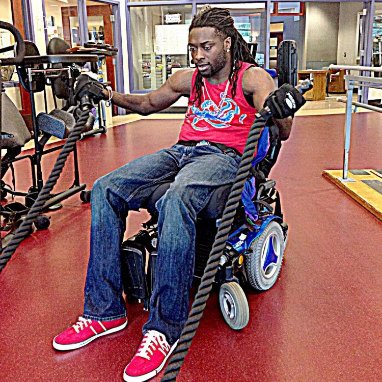 Nnaka works out in the gym while sitting in his wheelchair