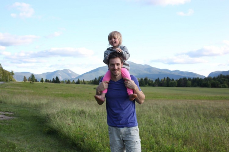dad with his daughter on his shoulders in field
