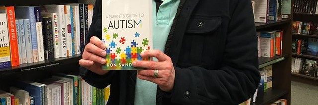Ron with his published book about autism.