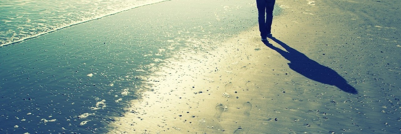 Person walking alone on sunny sandy beach with shells, foot prints and sea waves. Lonely walking on sea beach with waves at sunny day.