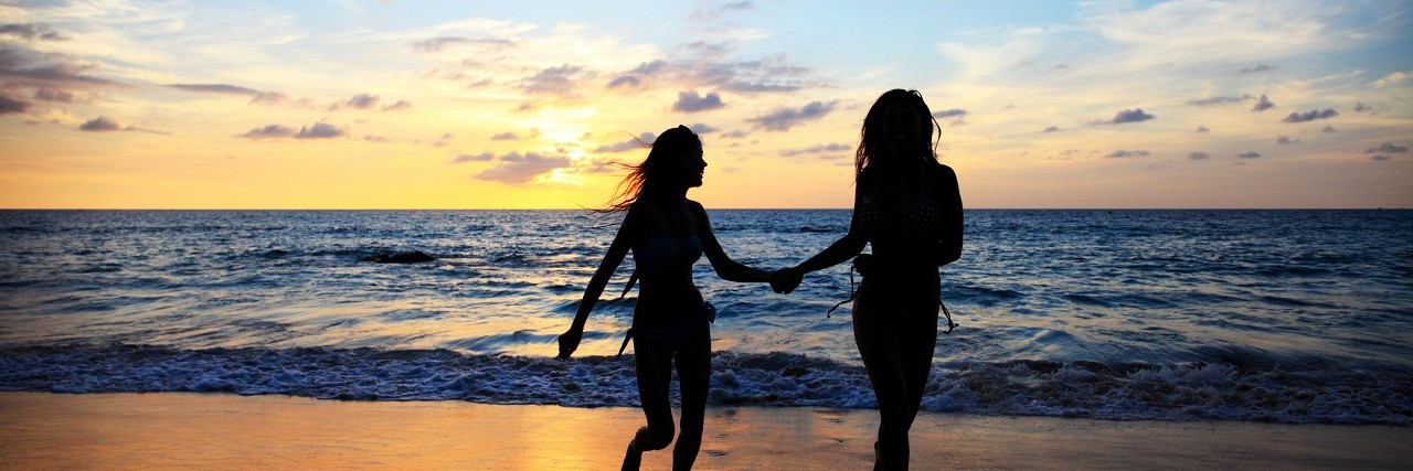 Two women walk together on the beach.