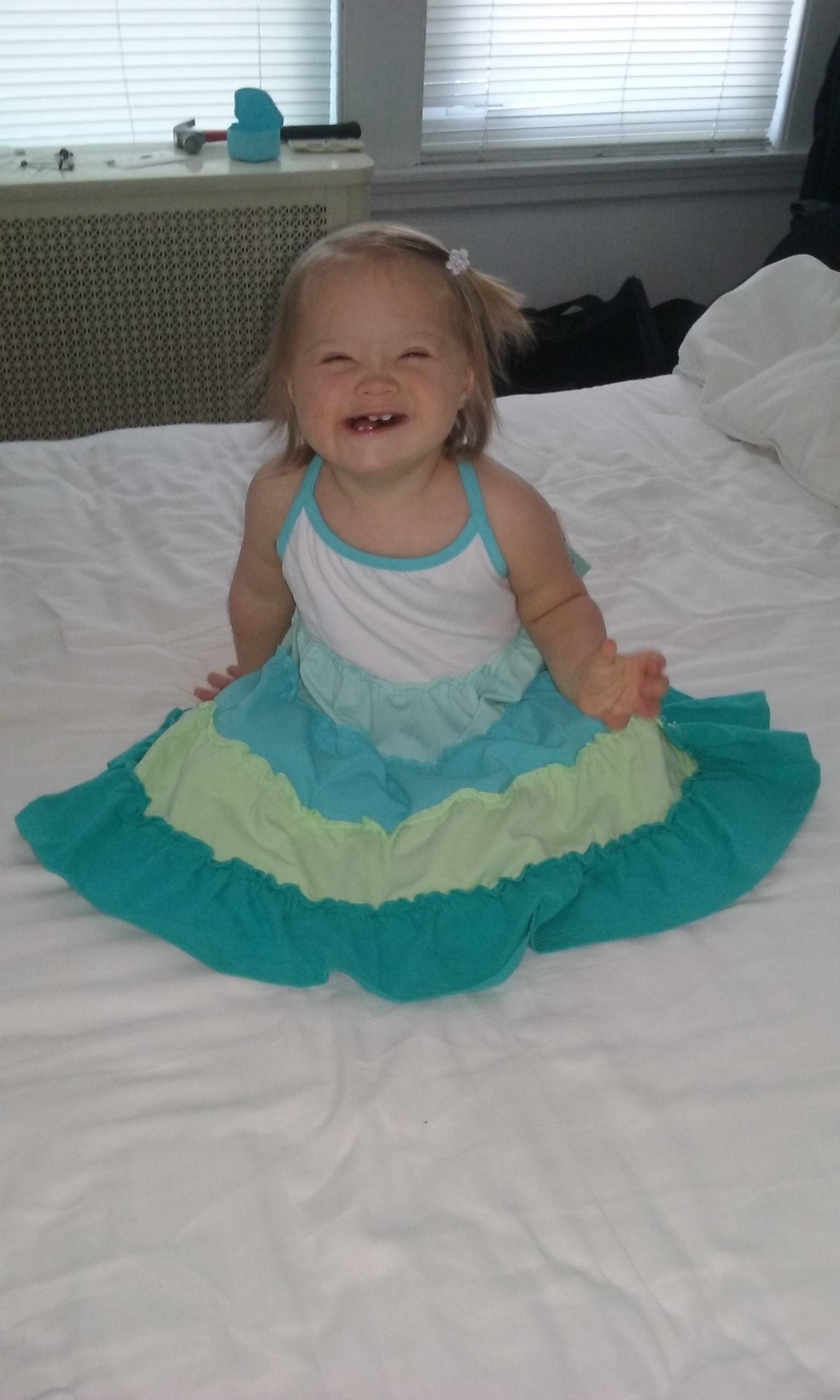 baby with down syndrome sitting on a bed smiling